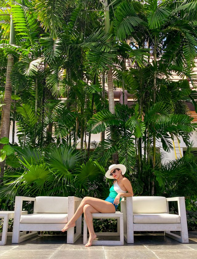 Girl wearing summer salt with a background of palm trees